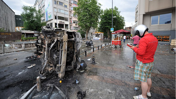 A protestor takes a photo of a burnt Turkish TV vehicle in Taksim square on June 2, 2013, after the clashes. (AFP Photo / Ozan Kose)
