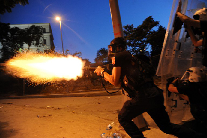 Turkish riot police officer fires tear gas during clashes with protestors between Taksim and Besiktas in Istanbul on June 3, 2013 during a demonstration against the demolition of the park. (AFP Photo / Bulent Kilic)