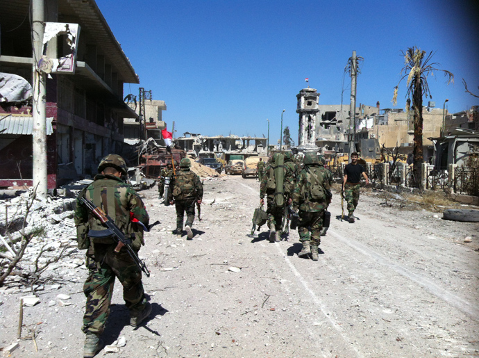 Syrian army's soldiers walk in a street left in ruins on June 5, 2013 in the city of Qusayr in Syria's central Homs province (AFP Photo / Str)