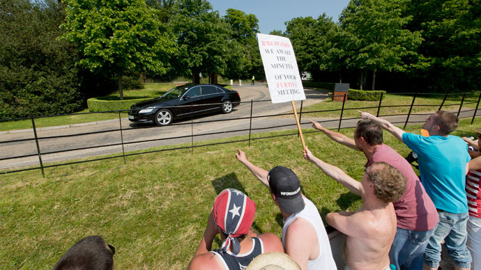 "Protesters shout and wave a placard that reads ""B'Bergers, we await the minutes of your furtive meeting"" as a vehicle arrives at the drive to the hotel where it is thought the 61st annual Bilderberg Meetings is taking place in Watford, north of London, on June 6, 2013.(AFP Photo / Justin Tallis)"