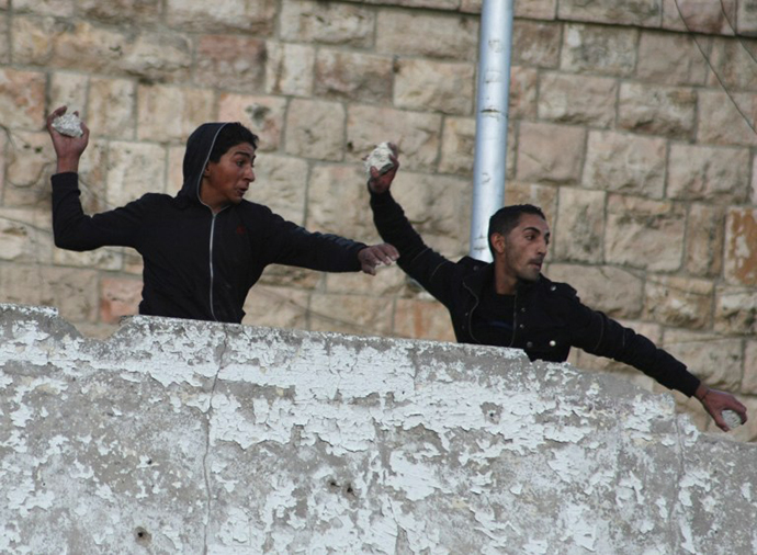 Palestinians throw stones towards Israeli soldiers at a check point guarding the Jewish settlements of Beit Hadasa and Beit Romano during clashes in the Israeli occupied West Bank town of Hebron. (AFP Photo / Hazem Bader)
