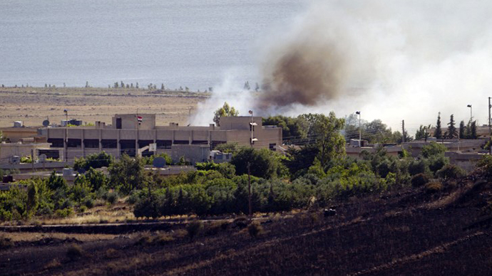 A picture taken from the Israeli side of the Israel-Syria ceasefire line in the Golan Heights shows smoke billowing from a fire caused by clashes between Syrian rebels and forces loyal to the regime on June 7, 2013 near the Quneitra crossing. (AFP Photo / Ahmad Gharabli)