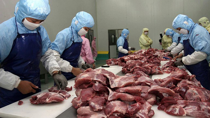 Workers cut up meat at a sausage factory in Xiamen, southeastern China's Fujian province. (AFP Photo)