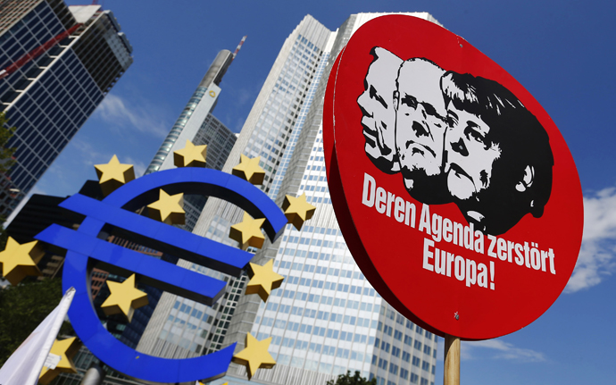 A sign depicting German Chancellor Angela Merkel (R) and other politicians is seen next to the Euro currency sign outside the European Central Bank (ECB) during a protest in Frankfurt, June 8, 2013. (Reuters / Ralph Orlowski )
