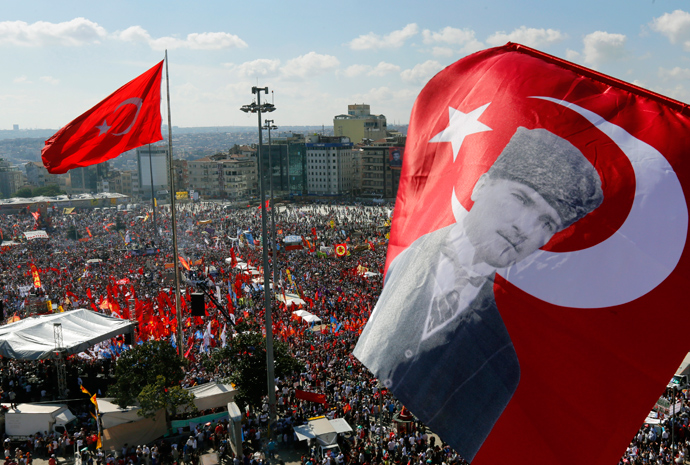 An anti-government protester waves a Turkish flag depicting the founder of modern Turkey Mustafa Kemal Ataturk as thousands of protesters gather in Istanbul's Taksim square June 9, 2013 (Reuters / Yannis Behrakis)
