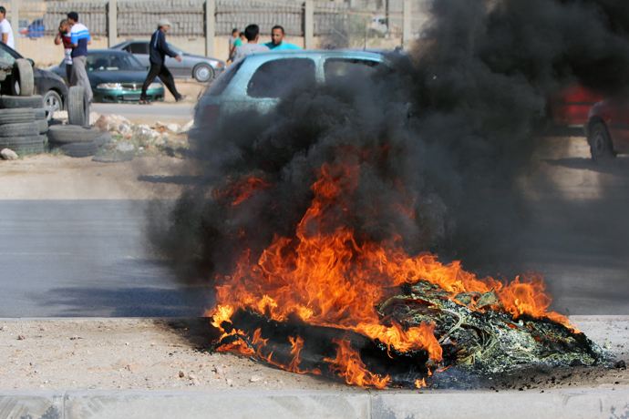 Tyres are burning during clashes between protesters and troops of the Libyan Shield Forces (LSF), a coalition of militias, following a demonstration outside the LSF office in the Libyan northern city of Benghazi on June 8, 2013 (AFP Photo / Abdullah Doma)