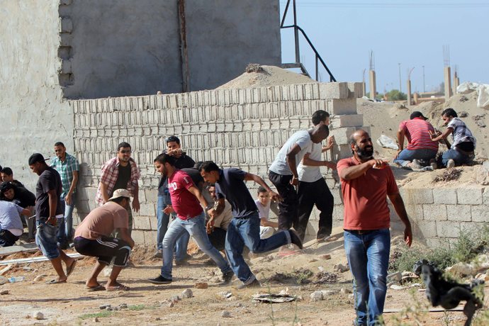Libyan protesters protect themselves behind a wall during clashes between demonstrators and troops of the Libyan Shield Forces (LSF), a coalition of militias, following a demonstration outside the LSF office in the northern city of Benghazi on June 8, 2013 (AFP Photo / Abdullah Doma)