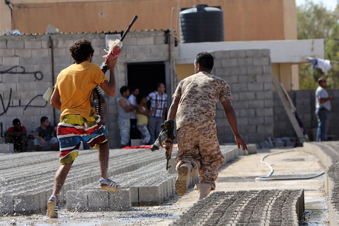Members of Libyan security forces run away holding weapons during clashes between protesters and troops of the Libyan Shield Forces (LSF), a coalition of militias, following a demonstration outside the LSF office in the northern city of Benghazi on June 8, 2013 (AFP Photo / Abdullah Doma)