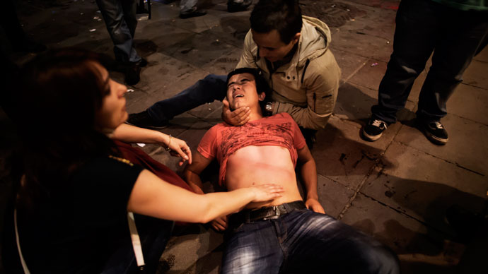 A beaten and shocked demonstrator cries in pain on June 9, 2013.(AFP Photo / Marco Longari)