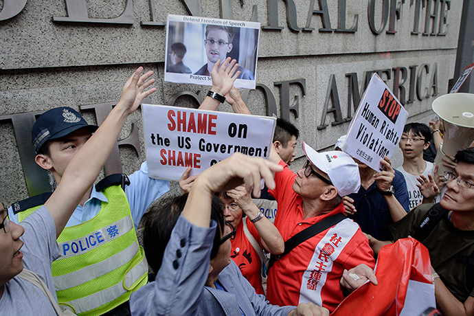 Protesters shout slogans as they hold up a picture of former US spy Edward Snowden in front of the US consulate in Hong Kong on June 13, 2013. (AFP Photo / Philippe Lopez)