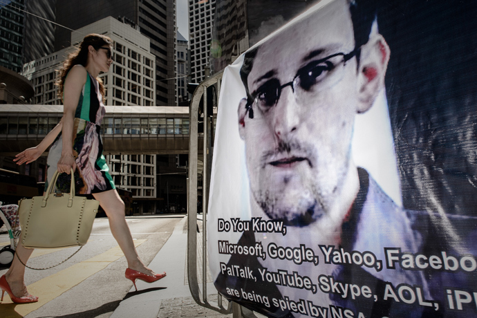 A woman walks past a banner displayed in support of former US spy Edward Snowden in Hong Kong on June 18, 2013 (AFP Photo / Philippe Lopez)