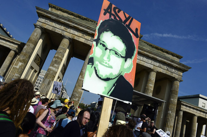 Demonstrators hold up a placard in support of former US agent of the National Security Agency, Edward Snowden in front of Berlin's landmark Brandenburg Gate as they take part in a protest against the US National Security Agency (NSA) collecting German emails, online chats and phone calls and sharing some of it with the country's intelligence services in Berlin on July 27, 2013. (AFP Photo)