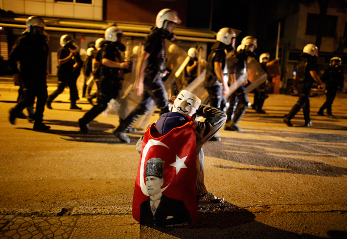An anti-government protester with a Guy Fawkes mask behind his head smokes a cigarette as he cleans his eyes after being hit with tear gas while riot police return to their position after chasing protesters in central Ankara June 11, 2013. (Reuters / Dado Ruvic)