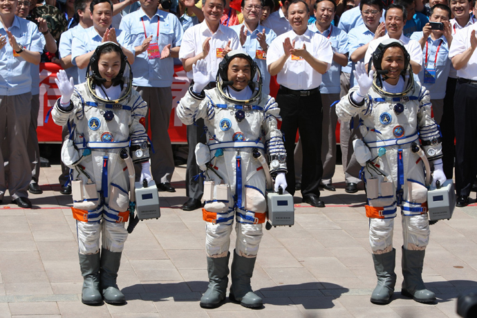 Chinese astronauts (L-R) Wang Yaping, Zhang Xiaoguang and mission commander Nie Haisheng wave to onlookers as they prepare to board the Shenzhou-10 spacecraft in Jiuquan, northwest China's Gansu on June 11, 2013 (China out / AFP Photo)