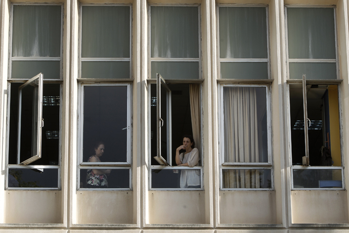 An employee smokes a cigarette at a window of Greek state television ERT headquarters after the government's announcement that it will shut down the broadcaster in Athens June 11, 2013. (Reuters / John Kolesidis)