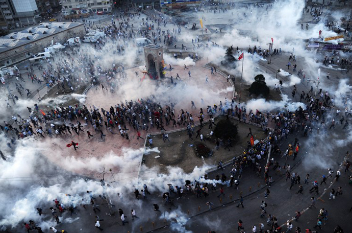 People run away as Turkish riot policemen fire tear gas on Taksim square on June 11, 2013. (AFP Photo / Bulent Kilic)
