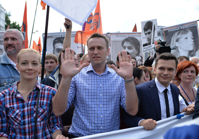 Oppositioner Alexei Navalny, center, and his wife, Yulia, and Ilya Yashin, right, member of the RPR-PARNAS federal political council's bureau, takes part in an opposition rally in Bolshaya Yakimanka Street in Moscow. (RIA Novosti/Iliya Pitalev)