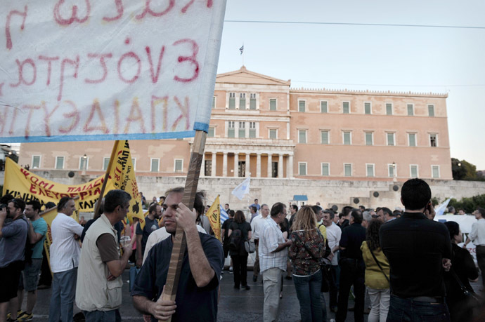 A Greek protestor holds a banner as he takes part in a demonstration in front of the parliament in Athens on May 31, 2013. (AFP Photo)