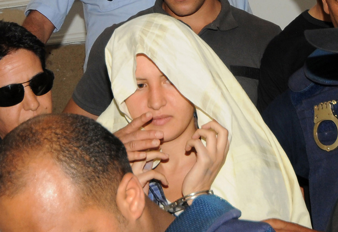 Amina Sboui (C), the Tunisian member of the Ukrainian feminist group Femen, appears handcuffed with a cloth over her head before an investigating judge at the courthouse of the central city Tunisian of Kairouan (AFP Photo)