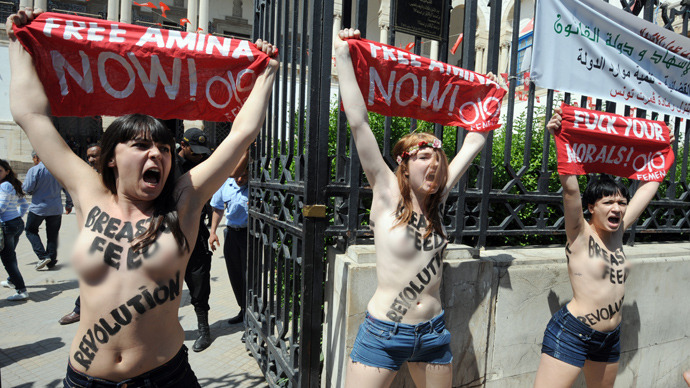 A file picture taken on May 29, 2013 shows three activists from the women's movement Femen demonstrating in front of the justice Palace in Tunis, before being arrested. The three women, two French and one German, face jail terms of up to a year when they go on trial in Tunis on June 5, although their lawyer is confident of a lighter sentence (AFP Photo / Fethi Belaid)