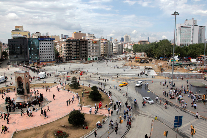 People walk at Istanbul Taksim square on June 12, 2013 after a large clean-up operation removed all evidence of the unrest, clearing the square of stray tear gas canisters, anti-Erdogan banners and makeshift barricades (AFP Photo / Gurcan Ozturk)