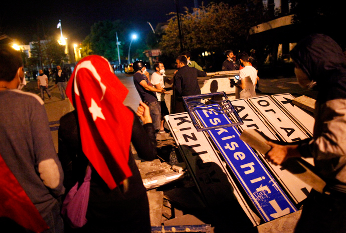 Anti-government protesters use road signs and cement blocks from a damaged sidewalk to set up a barricade, used to block riot police vehicles, during a protest in Kennedy street in central Ankara June 13, 2013 (Reuters / Dado Ruvic)