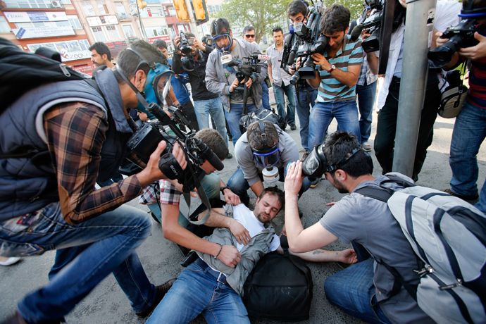 An injured journalist is filmed and helped by his colleagues during clashes between riot police and May Day protesters in central Istanbul (Reuters / Murad Sezer)