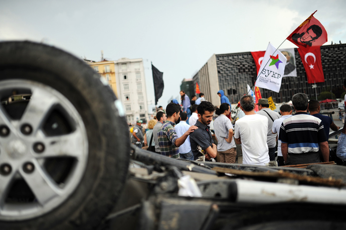 People look at Turkish riot policemen position at Taksim Gezi park in Istanbul on June 13, 2013 (AFP Photo / Bulent Kilic)