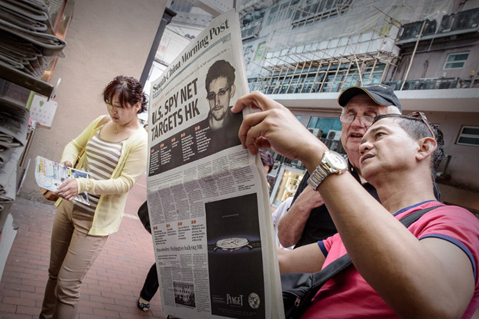 Two men read an edition of the South China Morning Post carrying the story of former US spy Edward Snowden on its front page in Hong Kong on June 13, 2013. (AFP Photo / Philippe Lopez)