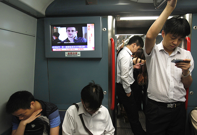 Passengers stand beside a TV screen broadcasting news of Edward Snowden, a contractor at the National Security Agency (NSA), on a train in Hong Kong June 13, 2013. (Reuters / Bobby Yip)