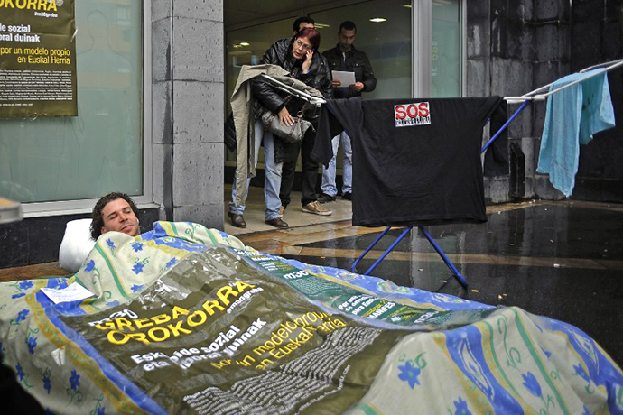 "A man lies on a camping mat installed in front of a Basque government's unemployment service ""Lanbide"" on May 22, 2013 in the Northern Spanish Basque town of Barakaldo. (AFP Photo / Rafa Rivas)"