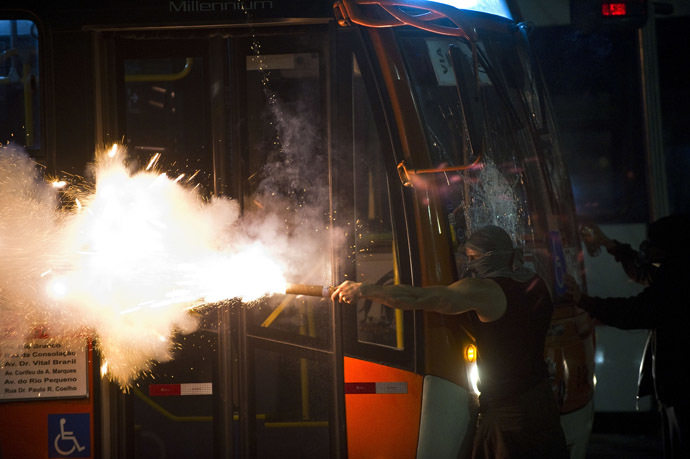 A demonstrator aims a flare at riot police during a demonstration in downtown Sao Paulo, Brazil on June 13, 2013, against a recent rise in public bus and subway fare from 3 to 3.20 reais (1.50 USD). (AFP Photo/Nelson Almeida)