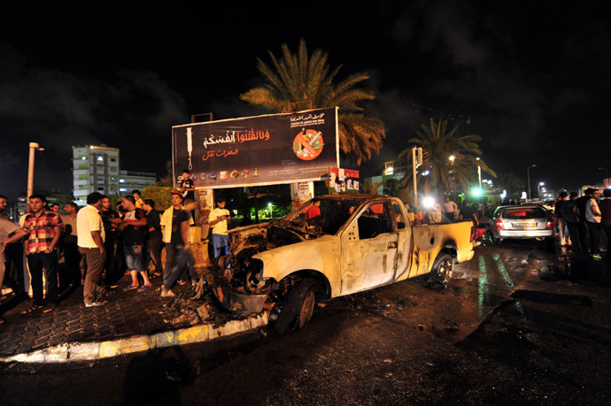 People gather around a burnt-out vehicle used by the Libyan Army's First Infantry Brigade, one of two military vehicles set on fire by protesters, in Benghazi June 14, 2013. (Reuters/Esam Al-Fetori)