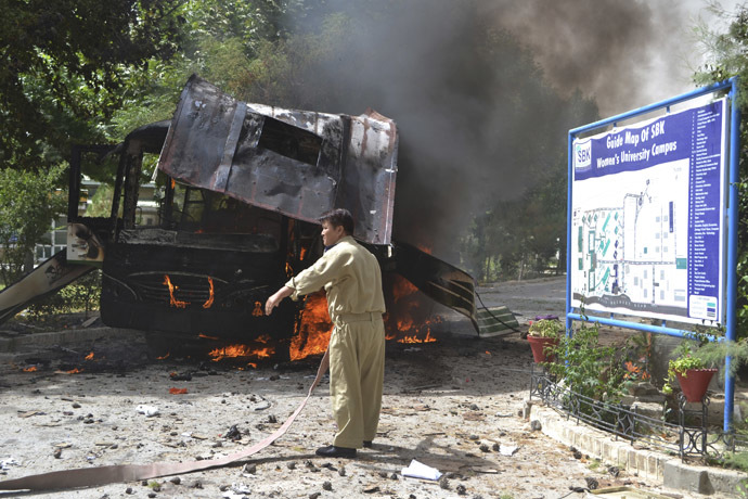 A firefighter stands near a burning bus after a bomb attack in Quetta June 15, 2013. (Reuters/Naseer Ahmed)