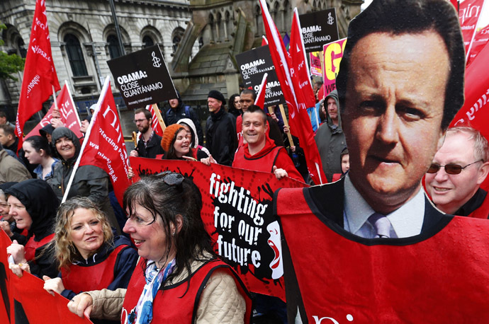 A demonstrator holds a placard depicting Britain's Prime Minister David Cameron (C) during a protest against the upcoming G8 summit, to be held near Enniskillen, in Belfast June 15, 2013. (Reuters)