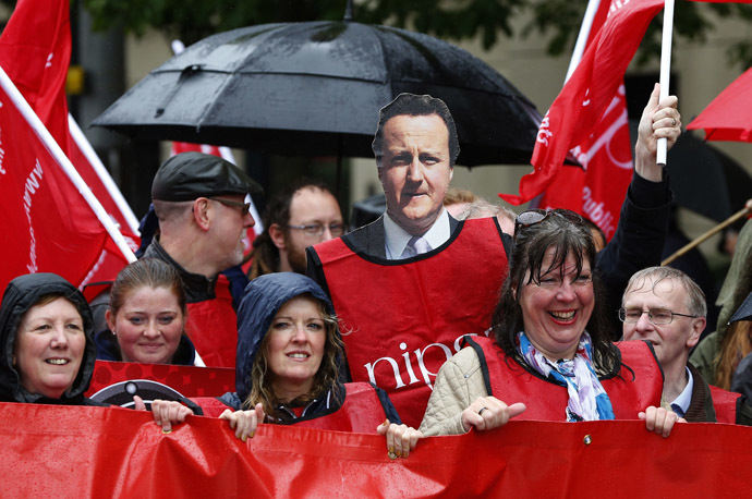 A demonstrator holds a placard depicting Britain Prime Minister David Cameron (C) during a protest against the upcoming G8 summit, to be held near Enniskillen, in Belfast June 15, 2013. (Reuters)