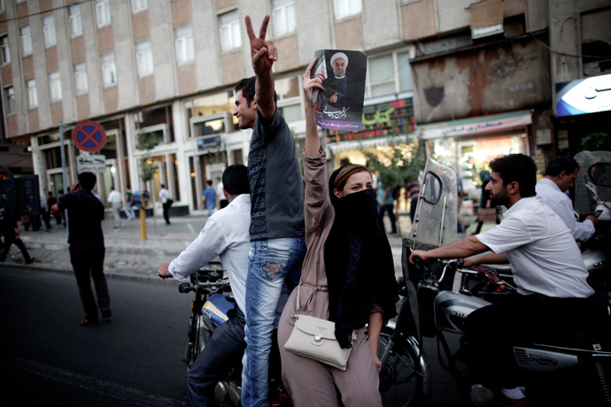 An Iranian woman holds a portrait of moderate presidential candidate Hassan Rouhani as she rides on a motorcycle along Valiasr street in Tehran on June 15, 2013 after he was elected as president (AFP Photo / Behrouz Mehri)