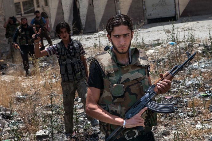 """Syrian rebel fighters belonging to the """"Martyrs of Maaret al-Numan"""" battalion leave their position after a range of shootings in the northwestern town of Maaret al-Numan in front of the army base of Wadi Deif, down in the valley (AFP Photo / Daniel Leal-Olivas)"""