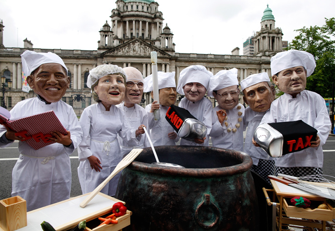 Oxfam charity volunteers wear masks depicting the G8 leaders around a large cauldron during a photo call to draw attention to the issue of world hunger outside City Hall in Belfast, Northern Ireland, on June 16, 2013 (AFP Photo / Peter Muhly)