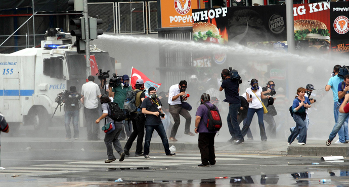Protesters escape from a water cannon as they clash with police during an anti-government demonstration in Ankara on June 16, 2013 (AFP Photo / Adem Altan)