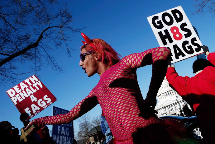 New York based drag performer Qween Amor dances during a rally while surrounded by protesters from the conservative Westboro Baptist Church in front of the U.S. Supreme Court in Washington, DC. (AFP Photo / Win Mcnamee)