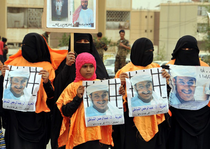 Relatives of Yemeni prisoner Abdel Rahman al-Shabati being held at the US-run Guantanamo Bay detention camp hold his pictures during a demonstration calling for the release of prisoners outside the US embassy in Sanaa on June 17, 2013. (AFP Photo / Gamal Noman)
