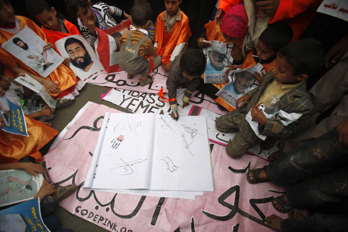 A boy, who is a relative of a Yemeni detainee at Guantanamo Bay prison, signs a letter demanding the closure of the prison, outside the U.S. embassy in Sanaa June 17, 2013. (Reuters / Khaled Abdullah Ali Al Mahdi)