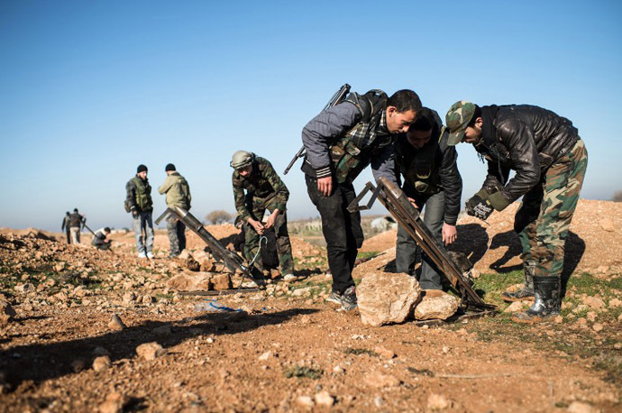 Syrian rebels prepare missiles for launch near the Abu Baker brigade in Albab, 30 kilometres from the northeastern Syrian city of Aleppo. (AFP Photo / Edouard Elias)