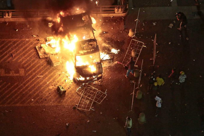 A vandalized press car from TV Record burns during a student demonstration in front of the City Hall in Sao Paulo, Brazil on June 18, 2013. (AFP Photo / Miguel Schincariol)