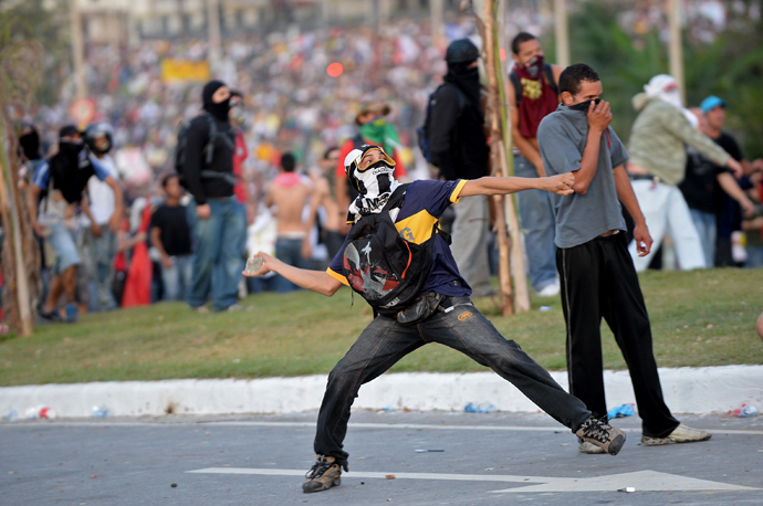 A demonstrator throws a stone against anti riot policemen during a protest against corruption and price hikes near Mineirao stadium in Belo Horizonte, Brazil on June 22, 2013 (AFP Photo / Nelson Almeida)