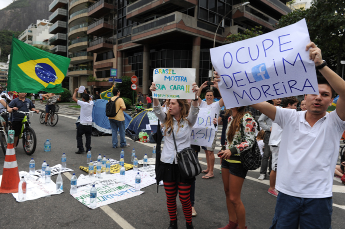 Protesters camping, since last night, in front of the residence of Rio de Janeiro's governor Sergio Cabral, in Leblon, Rio de Janeiro, hold signs while blocking the street on June 22, 2013 (AFP Photo / Tasso Marcleo)
