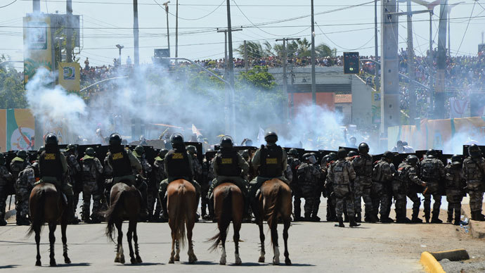 Riot police officers clash with protesters who blocked access to the Castelao Stadium in Fortaleza, where Brazil is to play Mexico in a FIFA Confederations Cup Brazil 2013 football match, to denounce the events' $15 billion price-tag, on June 19, 2013.(AFP Photo / Vanderlei Almeida)
