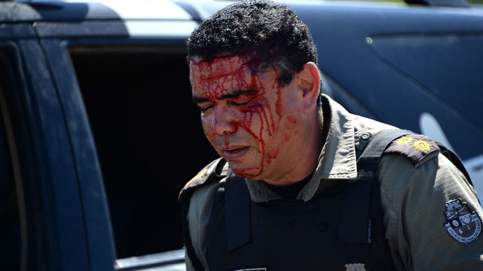 An anti-riot police officer walks in a street of Fortaleza after being injured during a protest against corruption and price hikes on June 19, 2013.(AFP Photo / Vanderlei Almeida)