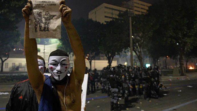 A man demonstrates near riot police officers after clashes erupted during a protest against corruption and price hikes, on June 20, 2013, in Rio de Janeiro. (AFP Photo / Lluis Gene)